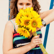 Portrait of brunette young woman holding bunch of yellow flowers — Stockfoto