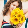 Brunette girl holding bunch of sunflowers — Stock Photo