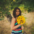 Beautiful young woman holding sunflowers in park — ストック写真