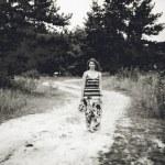 Photo of girl in long dress walking on road in field — Stock Photo #34753747