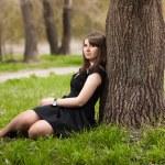 Brunette girl lying under tree in black dress — Stock Photo #34754411
