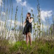 Young woman in black dress standing on glade — Stock Photo