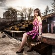 Woman in dress sitting on bench in old rusty building — Stock Photo