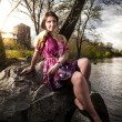 Girl in dress sitting on cliff on riverbank — Stock Photo