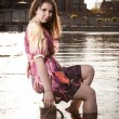 Romantic girl sitting on pier with legs in water — Stock fotografie