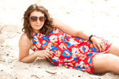 Girl in sunglasses and dress lying on beach — Stockfoto