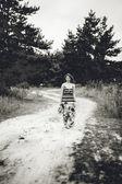 Photo of girl in long dress walking on road in field — Stock Photo