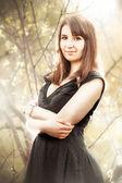 Jovem mulher vestida de preto posando contra arbustos — Fotografia Stock