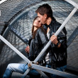 Man and woman hugging on street in metal cage — Stock Photo