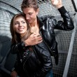 Man hugging sexy smiling woman near metal fence — Stock Photo