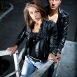 Sexy couple in leather coats posing on metal stairway — Stock Photo