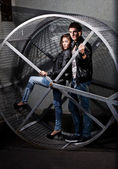 Couple in leather coat posing in metal construction on street — Stock Photo