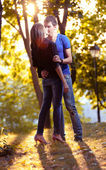 Young couple hugging at park in sun rays — Foto Stock