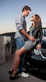 Macho hugging sexy girl on hood of the car — Stock Photo