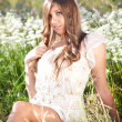 Girl with long hair sitting on meadow with white flowers — Stock Photo #35015091