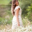 Woman in white dress walking on field full of white flowers — Stock Photo