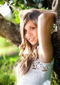 Retrato de uma linda garota sorridente, inclinando-se para a grande árvore — Fotografia Stock