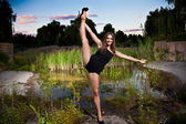 Flexible girl holding leg up against pond — Stockfoto