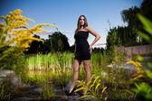Woman in black dress posing on riverbank — Stockfoto