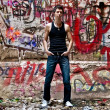 Muscular man in singlet posing against wall covered with graffiti — Stock Photo