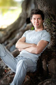 Portrait of muscular smiling man leaning to big tree — Stockfoto
