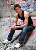 Man in black singlet sitting on concrete floor against graffities — Stock Photo