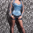 Stock Photo: Womin blue corset and stockings posing against wall
