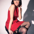 Woman in red dress and stockings sitting on bar chair — Стоковая фотография