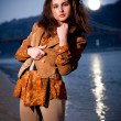 Brunette girl posing at evening against moonlight and sea — Stock Photo