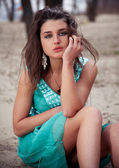 Sexy brunette girl in green dress sitting on sand — Stock Photo