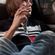 Young man smoking cigarette on back seat — Stock Photo
