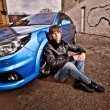 Man in leather coat sitting leaning to front wheel of blue car — Stock Photo