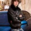 man in leather coat posing near blue car — Stock Photo