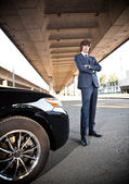 Young businessman posing near car against city landscape — Stock Photo