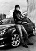 Portrait of handsome man in leather coat leaning to car — Foto de Stock
