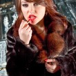Brunette woman in fur coat drawing lips with red lipstick — Stock Photo #35404569