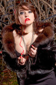 Brunette girl in fur coat drawing red line with lipstick on body — Stock Photo