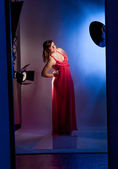 Young girl in long red dress posing in studio against flashes — Stock Photo