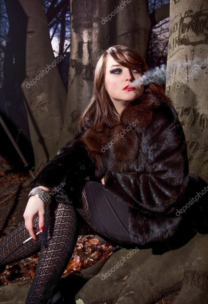 Woman In Fur Coat Smoking Cigarette While Sitting Near Big