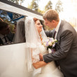 Groom cuddling young bride to white wedding limousine — Stock Photo