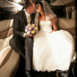 Newly married couple kissing on back seat of limousine — Stock Photo