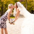 Portrait of bridesmaid kissing beautiful bride — ストック写真