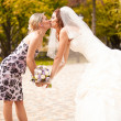 Portrait of bridesmaid kissing beautiful bride — Stock Photo