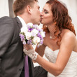 Bride kissing handsome groom while holding wedding bouquet — Stock Photo