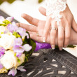 Portrait of groom holding brides hand on table near bouquet — Stock Photo