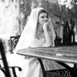 Portrait of young bride sitting at table at park — Stock Photo