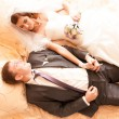 Newly married couple lying on bed and holding hands — Stock Photo