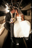 Newly married couple kissing on back seat of limousine — Stockfoto