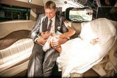 Bride lying on grooms legs on limousines back seat — Stock Photo