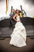 Bruid en bruidegom poseren tegen grote bulldozers emmer — Stockfoto
